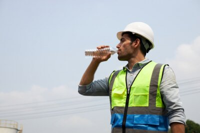 Obraz The young engineer drinks water to quench his thirst.