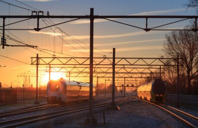 Obraz Trains leaving a station during a winter sunrise.