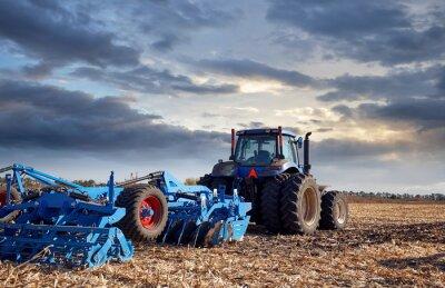 Obraz Traktor pracuje na poli při západu slunce