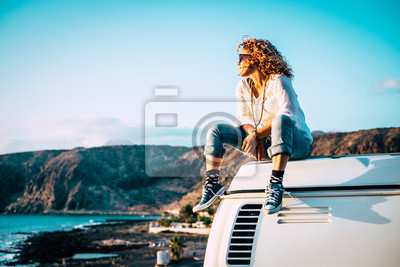 Obraz Travel concept with independent people enjoyig the outdoor leisure activity and wanderlust life lifestyle - woman sit down on the roof of a old nice vintage camper van