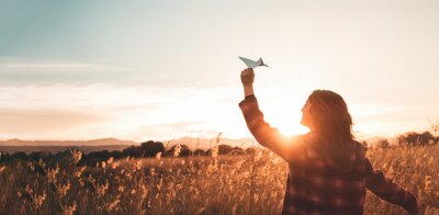 Obraz Travelling woman with paper airplane enjoying life and freedom at the land at sunset. Arms outstretched and happiness