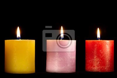 Tři svíčky na černém pozadí.