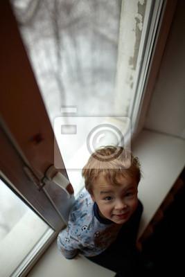 Usmívající se chlapec seděl na okenním parapetu.
