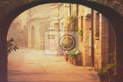 Úzké ulice středověkého města San Quirico d'Orcia s obloukem, zelenými rostlinami a dlažební kostky, cestovat mlhavého rána Itálie pozadí. Vintage bederní styl.