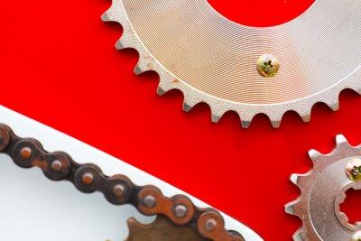 Obraz Válečkové řetězy s řetězovými kolečky pro motocykly na červeném pozadí