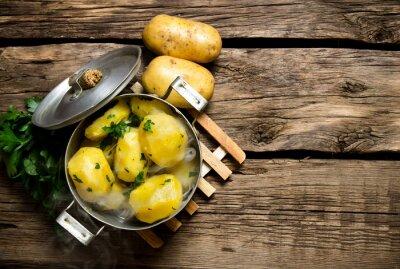 Obraz Vařené brambory s bylinkami na dřevěném stole. Volný prostor pro text.