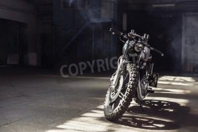 Obraz Vintage motocyklu stojící v temné budově v paprscích slunečního světla. Tónované barvy. Čelní pohled