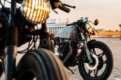 Obraz Vintage vlastního motocyklu Cafe Racer motorka s svítí kontrolka zapnutí. Jeden s grilem světlometů jiným s páskou křížem přes optiku na prázdném parkovišti na střeše při západu slunce. Bederní životn