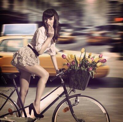 Obraz vintage žena na kole v ulicích města s taxíkem