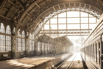 Obraz Vlakové nádraží vnitřní západ slunce východ slunce v sépii. Vozík a plošina s konstrukční střechou. Cestujte vlakem po železnici