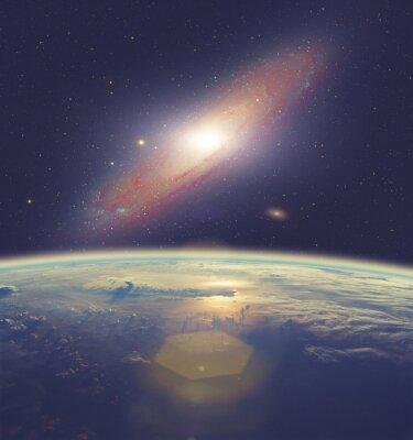 Obraz Východ slunce nad Zemi s velkou galaxií v Andromedě.