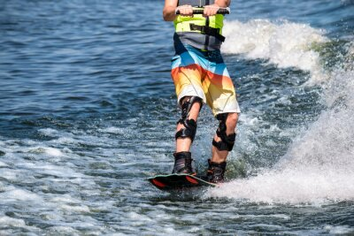 Obraz Wakeboard. Athlete's feet on the board on the wave. Special equipment for fixed knees