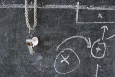 Obraz whistle of soccer or football referee on a black board with tactical diagram