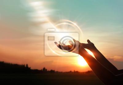 Obraz .Woman ruce se modlí za požehnání od Boha na pozadí při západu slunce