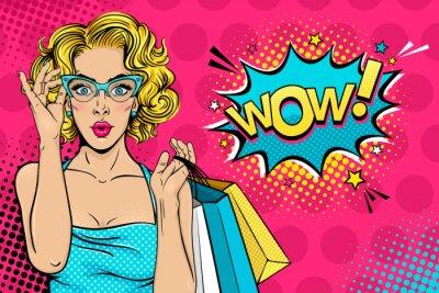 Obraz Wow ženská tvář. Sexy překvapeně mladá žena v brýlích s otevřenými ústy a blondýna kudrnaté vlasy drží nákupní tašky a Wow! řečová bublina. Vektorové světlé pozadí v pop art retro komické styl.