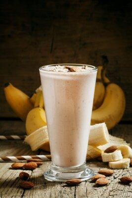 Obraz Banán smoothie s mlékem, mleté mandle ve velkém šálku na straně