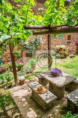 Zahrada je plná květin a vinné révy v Toskánsku