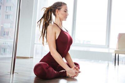 Obraz Zaměřena hezká žena dělá jógu ve studiu