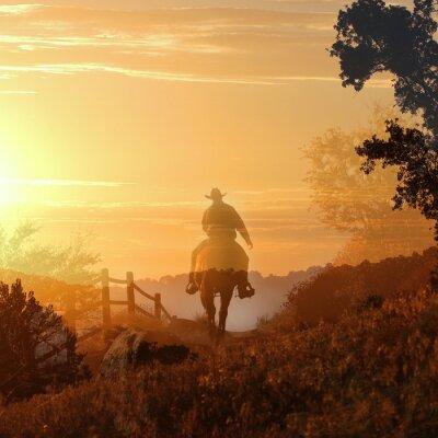 Obraz Západ slunce Cowboy. Kovboj jezdí pryč do západu slunce v průhledných vrstvách oranžové a žluté mraky, plotem a stromy.