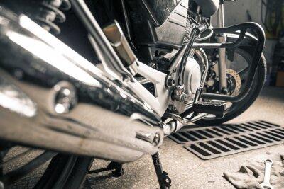 Obraz Zblízka mužských rukou s motocyklem v garáži