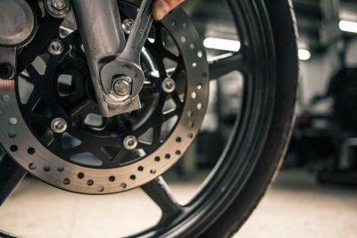 Obraz Zblízka ruky člověka drží montážní klíč v blízkosti vozidla motocyklu.
