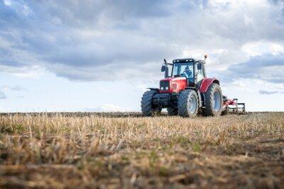 Obraz Zemědělské stroje v popředí provádět práci v terénu.