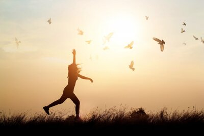 Obraz Žena a létající ptáky těší život v přírodě na západ slunce na pozadí