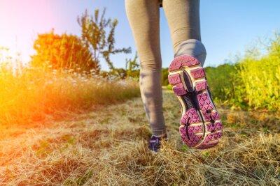 Obraz Žena běží při západu slunce v poli