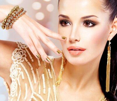 Obraz Žena se zlatými drápy a krásné zlaté šperky