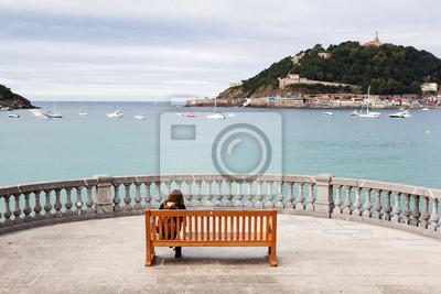 Žena sedící na lavičce v San Sebastian.