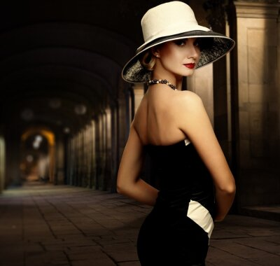 Obraz Žena v černých šatech a sám velký bílý klobouk venku v noci