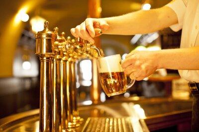 Obraz zlaté pivo v ruce a pivo, pípy