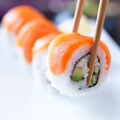 Obraz zvedl kousek sushi s hůlkami