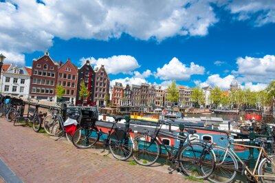 Plakát Amsterodam, Nizozemsko 27.dubna: Tradiční Amsterdam panoráma s středověký domy, kola na můstku dubna 27.2015. Amsterdam je nejlidnatějším městem Nizozemského království.