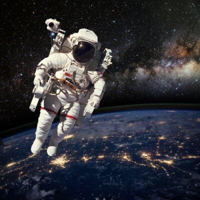 Plakát Astronaut ve vesmíru nad zemí během noční doby. Elem