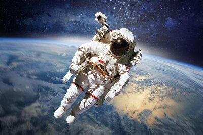 Plakát Astronaut ve vesmíru s planetě Zemi jako pozadí. Prvky