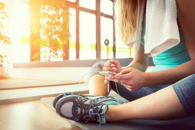 Plakát Atraktivní blondýna s chytrý telefon, odpočívá po zacvičit si v posilovně