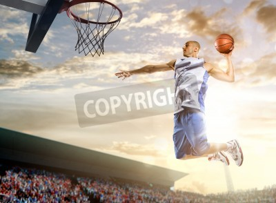 Plakát Basketball player in action on background of sky and crowd