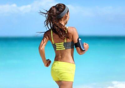 Plakát Běh Motivace - běžec trénink s hudbou při pohledu zezadu běhání v módě žluté pásky sportovní podprsenky a neonové šortky oblečení nosit bezdrátová sluchátka na letní beach pozadí.