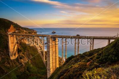 Plakát Bixby Bridge (Rocky Creek Bridge) a Pacific Coast Highway při západu slunce blízko Big Sur v Kalifornii, USA. Dlouhé vystavení.