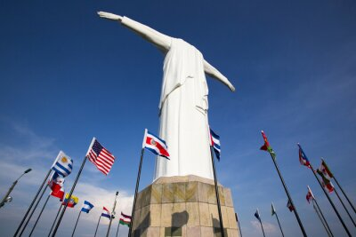 Plakát Cristo del Rey statue of Cali with world flags and blue sky, Col