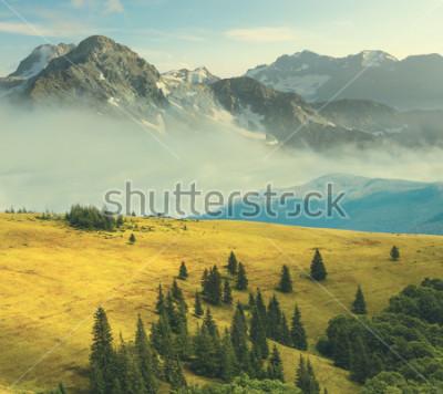 Plakát horská krajina, skalnatá hora v mlze ohromit travnaté kopce