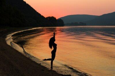 Plakát Krásná a sexy dlouhé vlasy žena na pláži západu slunce