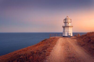 Plakát Krásný bílý maják na pobřeží oceánu při západu slunce. lan
