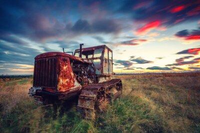 Plakát Krásný západ slunce nad polem a staré rezavé traktoru