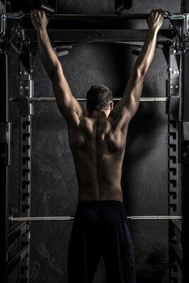 Plakát Kulturistika, mladé atletické silný muž ukazuje zádové svaly pracují na Fitness-bar, velký kontrast s Desaturated Grunge filtrem