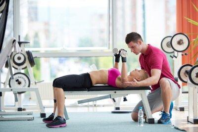 Plakát Mladá sportovní žena s trenérem cvičení břemen