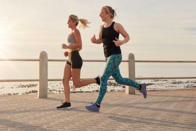 Plakát Mladé ženy běží podél pobřežní promenádou