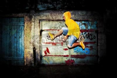 Plakát Mladý muž skákání / tančí na grunge graffiti zeď pozadí
