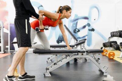 Plakát Mladý muž trenér dává pokyny, se ženou v tělocvičně